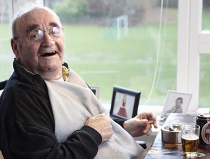 Glad ældre mand nyder en øl på plejehjem