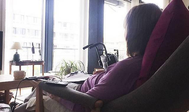 Ældre kvinde med parkinsons sidder i stol og kigger ud af vinduet