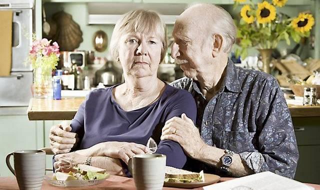 Ældre bedrøvet ægtepar sidder ved spisebordet
