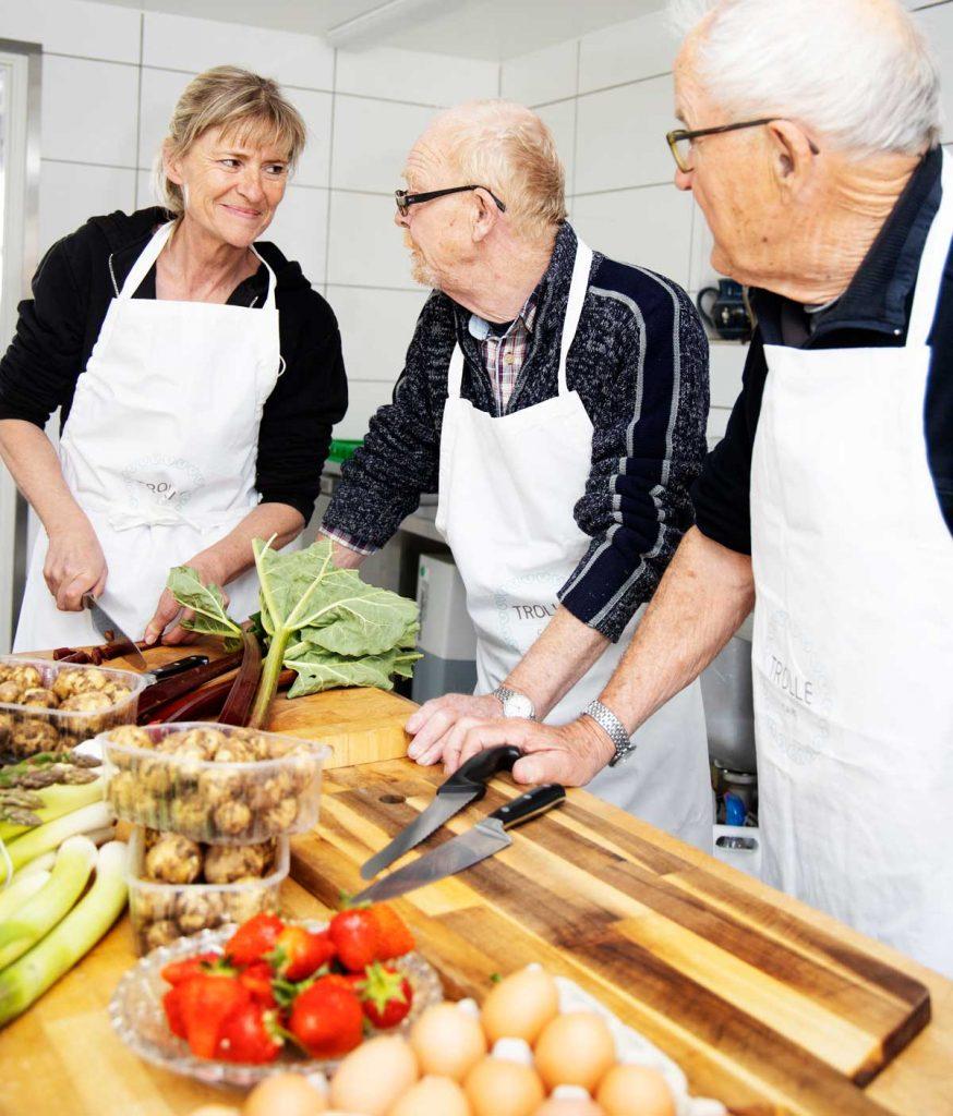 Ældre kvinde og to ældre mænd står i køkkenet og laver mad