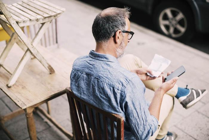 Mand sidder på en fortovscafé og kontakter Trollecare på telefon