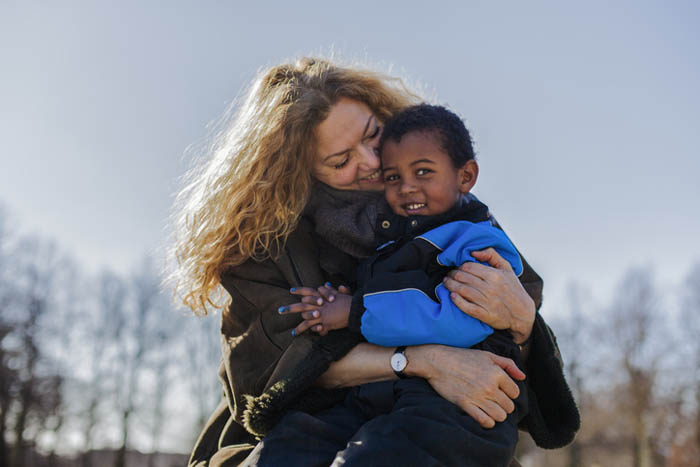 Smilende kvinde omfavner et barn i flyverdragt
